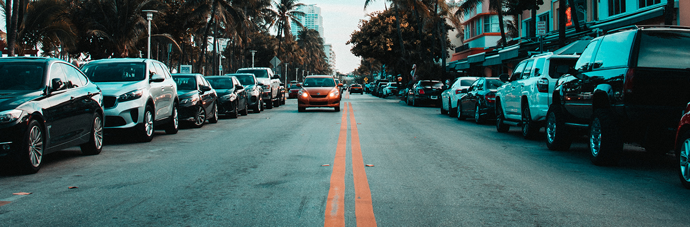 An orange car travelling a street in Miami